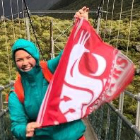 Udall 2018 recipient Emma R. Johnson holding up a cougar flag while studying abroad in New Zealand.