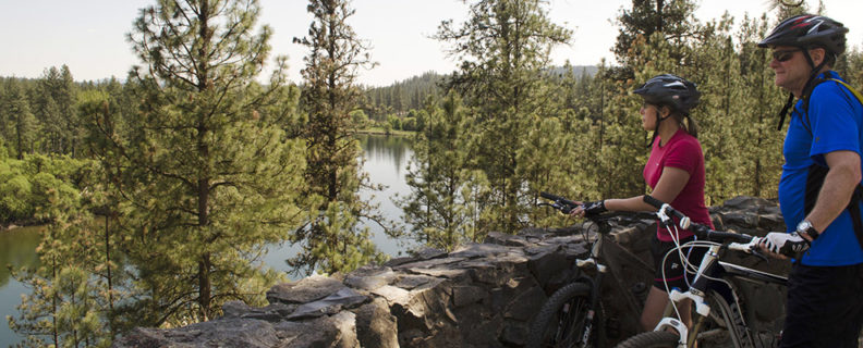 two bicyclists pause to look at the Spokane River while riding in Riverside State Park