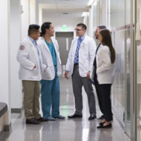 Medical students standing talking at their lockers in PBS
