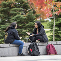 Two students sitting outside talking