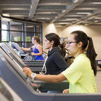 Three students exercising in the fitness center
