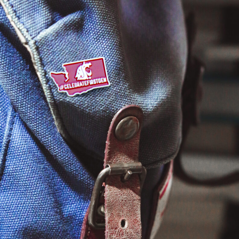 The first-generation lapel pin shown on a backpack. The pin displays the hashtag #CELEBRATEFIRSTGEN.