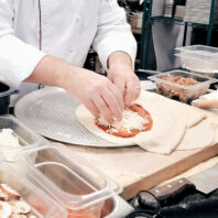 Jamie Callison, Hospitality and Business Management executive chef and director of the Marriott Foundation Hospitality and Culinary Innovation Center, prepares a pizza in Todd Hall's commercial kitchen.