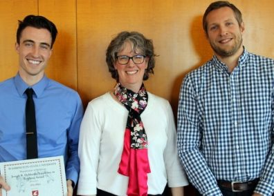 While receiving the DeMartini Teaching Award, Eric Allen, holding an award, stands to the left, Jake Hammond stands to the right, and award presenter, Professor and Department Chair, Monica Kirkpatrick Johnson stands in the center, all three are smiling at the camera.