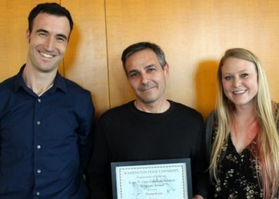 Tom Rotolo, standing in the center, receives the Louis N. Gray Student Advocate Award from Adam Roth, standing to the left, and Sadie Ridgeway standing to the right, all three are smiling at the camera.