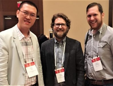 Alumni Feng Hao, standing to the left, Kyle Knight, standing in the center, and Pierce Greenberg, to the right, are standing together at the 2018 ASA meeting in Philadelphia, all three are smiling at the camera.