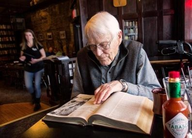 Jim Short is sitting at a table in Rico's Pub browsing through the encyclopedia.