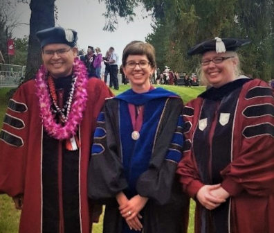 Two graduating PhD students, Jose Collazo, to the left, and Valerie Adrian, to the right, stand with their professor, Julie Kmec, who is standing in the center, all three are wearing commencement regalia and are standing together outside, after the graduation ceremony, all three are smiling at the camera.