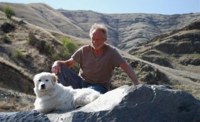 A photo of Lew Carter and his dog resting during a hike.