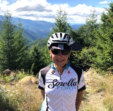 Front facing photo of Amy Wharton, standing on a mountain-top in Oregon, wearing a helmet and bicycling clothes.