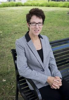 Front facing photo of Sharon Bird, sitting on a bench.