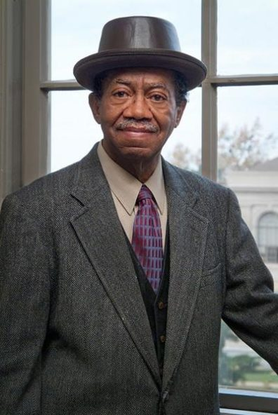 Gordon shown from the waist up, wearing a tweed jacket, white button-down, a tie, and a brown pork-pie hat. He is standing in front of a window, looking into the camera, and smiling.
