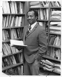 A younger Gordon Morgan shown standing, from the knees up, wearing a suit. Gordon is standing among shelves filled with books and papers. He is holding an open book in one hand, his other hand is in his pocket. He is looking at the camera and smiling. The photo is black and white.