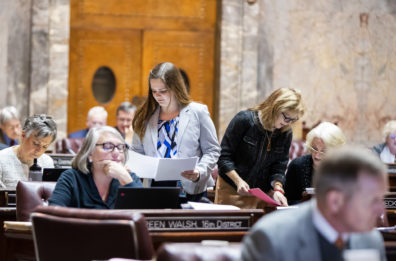 Alex shown standing in the middle of several desks where legislative members are sitting and working. Alex is passing out papers. She is wearing a white jacket and a white, blue, and black blouse.
