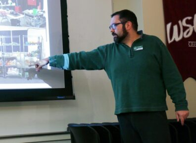 Joe is standing and pointing towards an image on a projected screen.