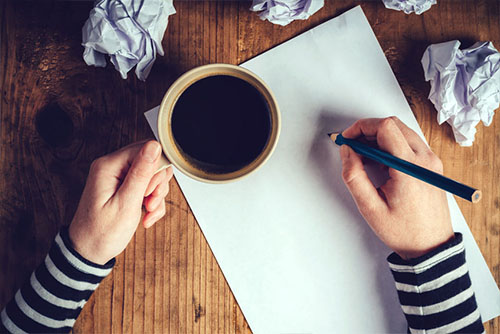 Writing on a blank piece of paper with coffee