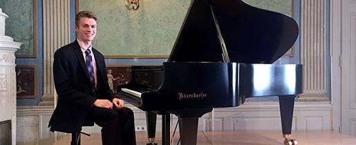 Garrett Snedeker sitting by a piano.