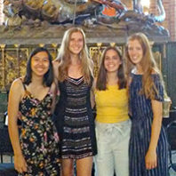 4 students standing before a large scultpure.