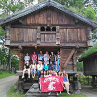 Group of students holding the WSU Cougar flag, sitting on the porch of a large wooden building.