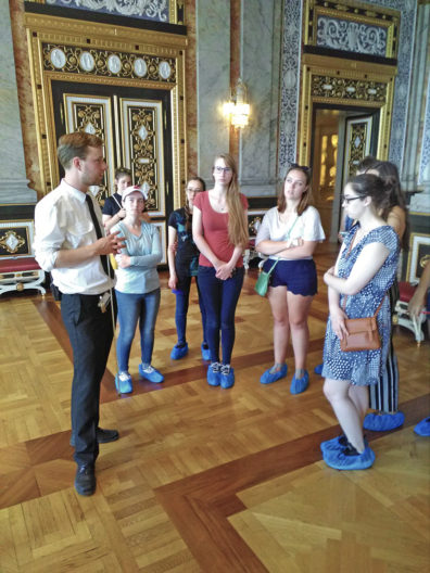 Students wearing shoe covers on the polished wooden floor in the Christiansborg Palace. Decorative gold frames line the doors on the marbled walls.