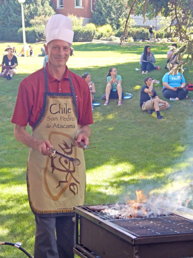 Dean Norton at the BBQ grill with students behind on the lawn.