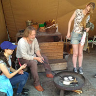 Students look on as a resident demonstrates how bread can be backed in a large pan over an open fire..