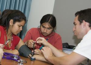 Native American students take each other's blood pressure during a Na Ha Shnee camp.
