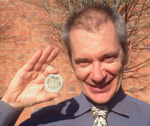 "Thomas Gazzola with the winning ""Nautilodestone"" coin from the MIT Mystery Hunt. Photo courtesy WSU Vancouver."