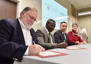 Rand Wortman, Wayne Martin, H. Keith Moo-Young and Lura Powell​ sign the partnership agreement.