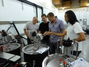 Mark Holst (far left) and Babak Taheri (far right), Cypress Semiconductor Corp., setting up the new wine fermentation system with Washington State University staff Richard Larsen (middle left) and Philip Teller (middle right).