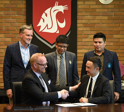Chris Meiers, WSU Tri-Cities vice chancellor of enrollment management and student services, and Nitiphong Songsrirote, dean of the Mahasarakham Business School, shake hands
