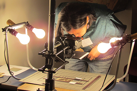 An SHN workshop participant peers through a camera attached to a copy stand during training in image digitization and preservation at the University of Alaska Fairbanks.