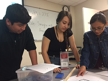 Dare to Dream Academy mentor Celeste Estrada, center, encourages high school participants in project work.