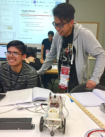 Edgardo Quiroz assists Dare to Dream Academy student with robotic project programming