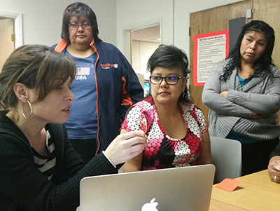 Kim Christen (left), Zuni Public Library's Jennifer Lonjose (seated) and two community members discuss aspects of a photograph identification project in Zuni, NM.
