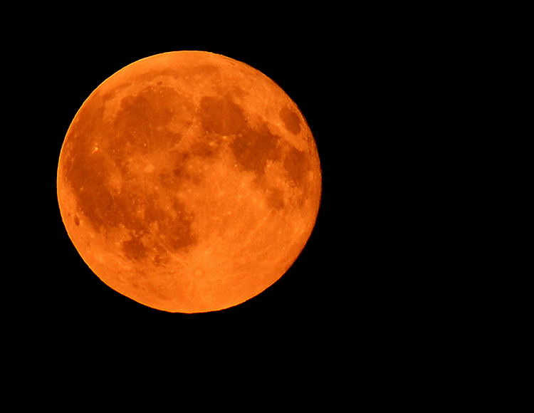 Harvest full moon appears orange-red due to harvest particulate and smoke from area fires.