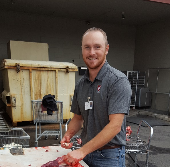 Nursing student Mike Mosier at makeshift butcher table