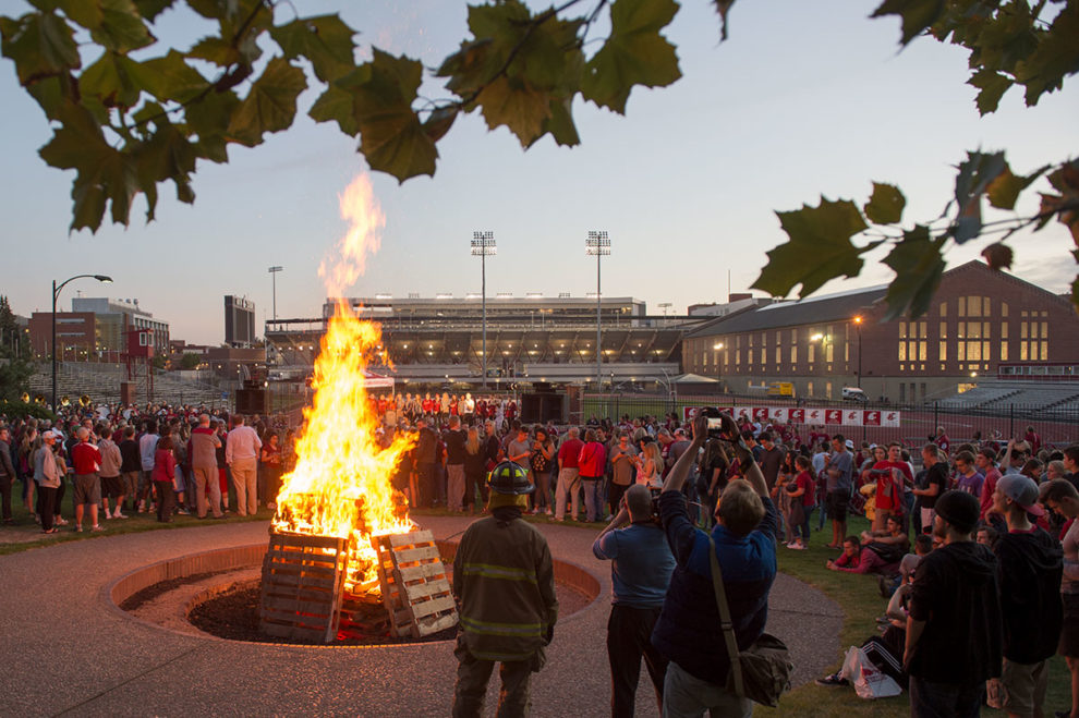 Crowd standing around bonfire with Martin Stadium and Hollingbery Fieldhouse in the background.