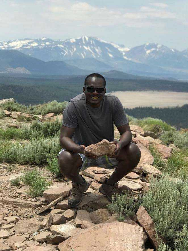 Lambert Ngenzi in the California White Mountains holding a rock with the mountains in the background.