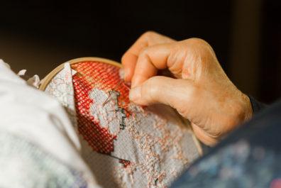 Elderly hands working on cross-stitch needle work.