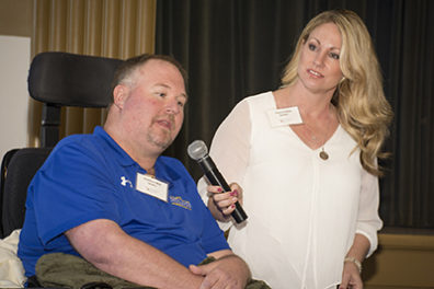Assisted by his wife Theresa, Matt Wild talks about life with ALS during the symposium's clinical problems discussion panel.