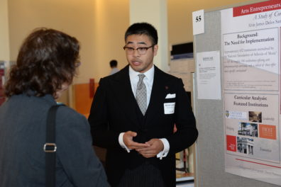 Male student presenting poster showing research to female judge.