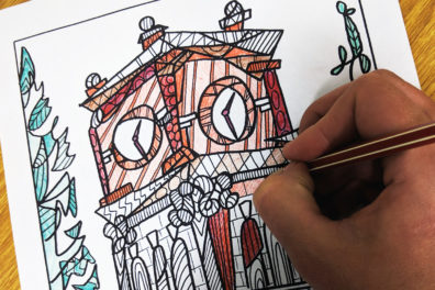 A person coloring a custom image of Bryan Hall.