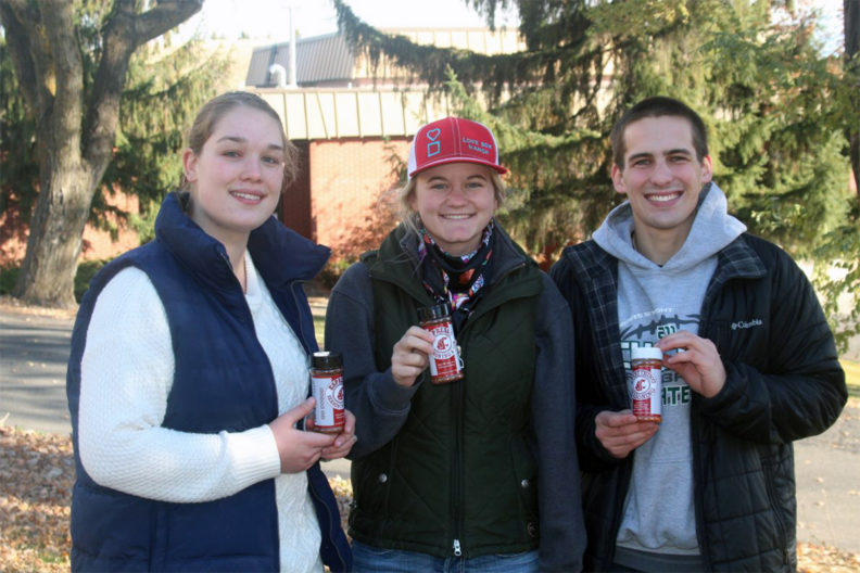 Three students holding seasoning side by side.