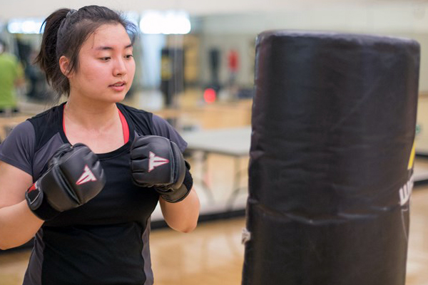 Gym goer with sparing gloves on prepares to hit a punching bag in the sweat the stress class