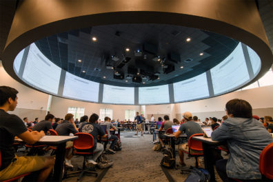 Students sit at desks facing a center projection system while a student speaks in the middle