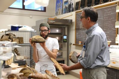 Stephen Jones examines different breads with a bread lab student