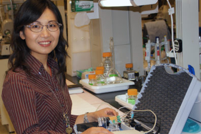 Annie Du in profile while handling a wire on a mechanical and materials engineering project
