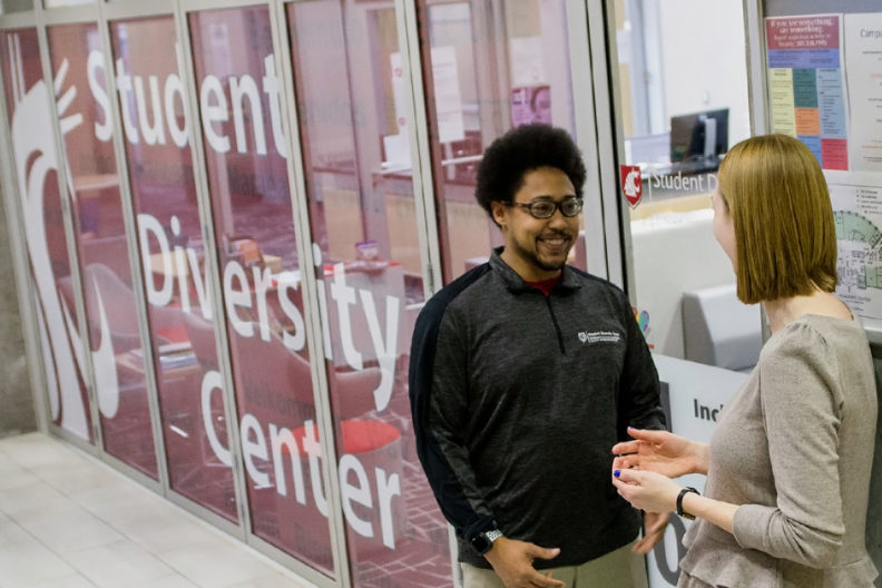 Students standing outside the new lounge and offices for WSU Spokane's offices of Community Engagement and Service Learning, Student Leadership and Involvement, and the Student Diversity Center.