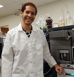 Korey_Brownstein: Korey Brownstein, a graduate student in the WSU Molecular Plant Sciences Program, stands in front of a liquid chromatography-mass spectrometry machine used to detect nicotine residue in ancient dental plaque.
